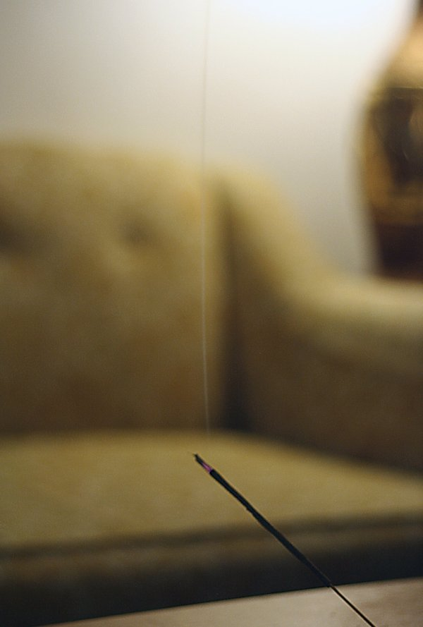 incense burning in front of soft focus vintage furniture
